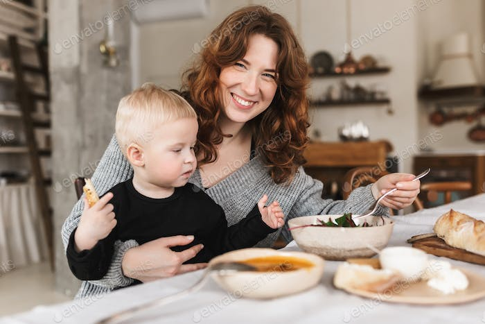 Mom spending time with baby boy in cozy kitchen at home