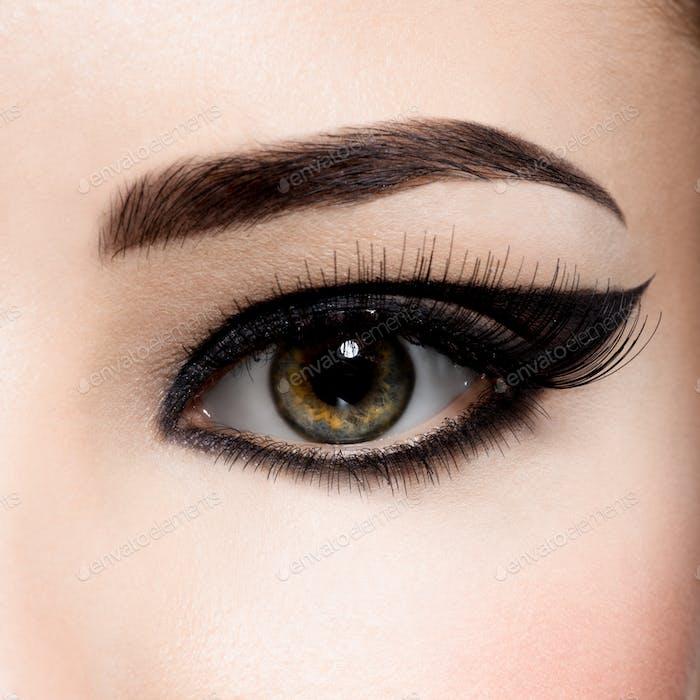 Closeup female eye with creative fashion make-up. brown eyeshadow