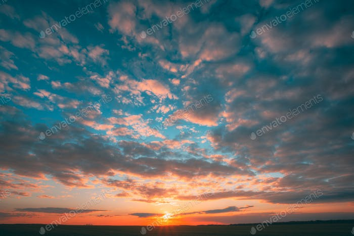 Sunset Sunrise Over Field Or Meadow. Bright Dramatic Sky And Dar