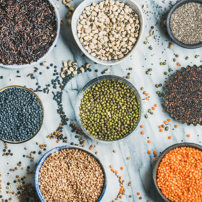 Various raw uncooked grains, beans, cereals, marble background, square crop
