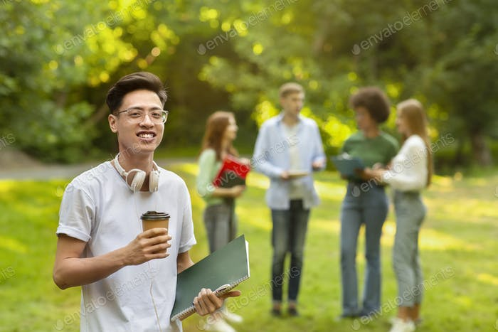 Campus Life. Asian Student Guy Posing With Notepads And Coffee At Campus