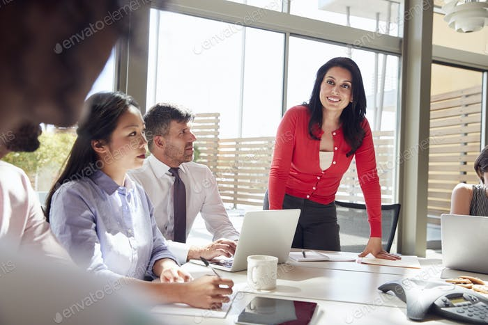 Smiling businesswoman listening to colleagues at a meeting
