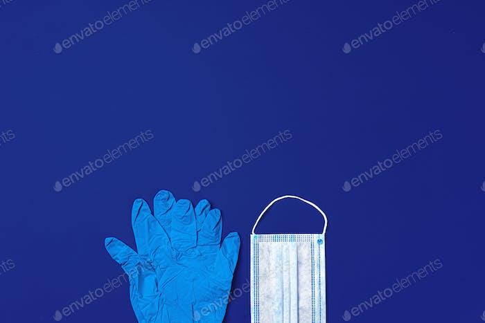 Medizinische Handschuhe und chirurgische Schutzmaske auf dunkelblauem Hintergrund