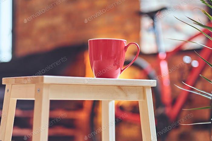 Nahaufnahme Bild der roten Kaffeetasse auf einem Tisch.