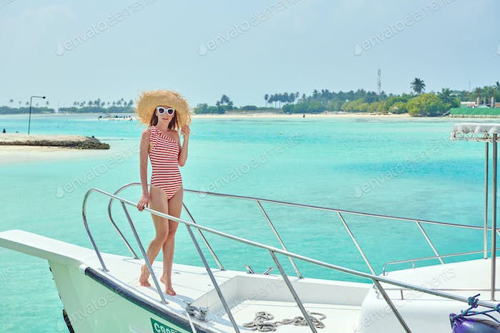 Woman in red bikini standing on boat bow