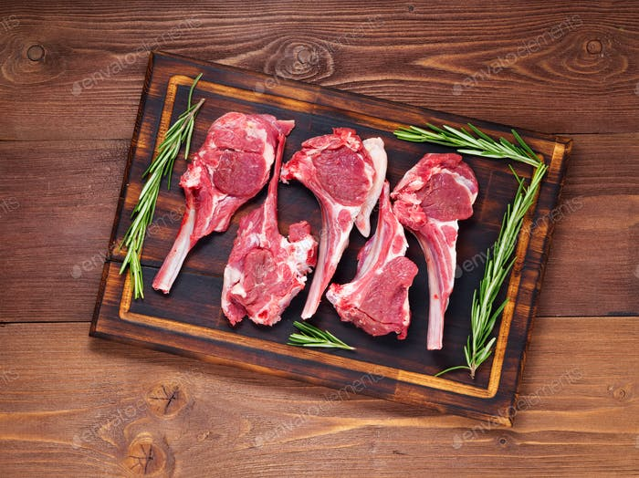 Raw lamb cutlets on bone on dark brown wooden background, lamb ribs, top view.