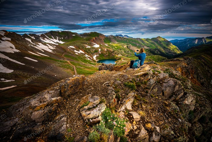 Tourist admires view from California Pass towards lake Como and