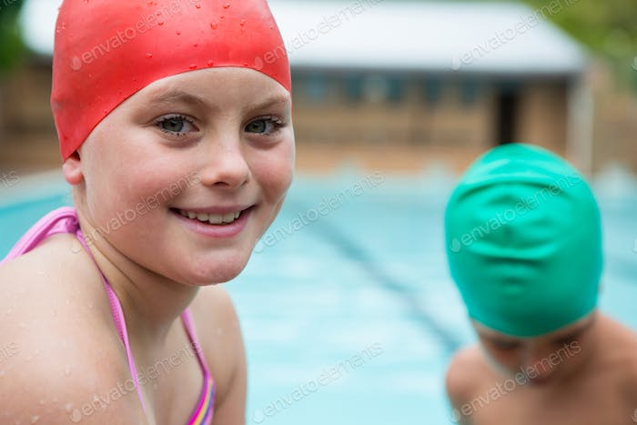 Smiling girl with swim cap near poolside