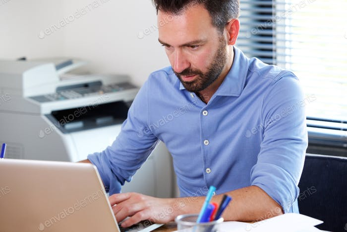 Mature business man working on laptop