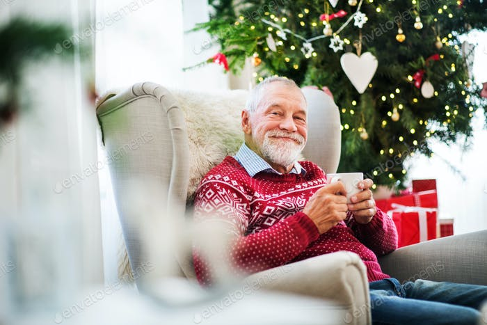 Thumbnail for A portrait of senior man with a cup sitting on armchair at home at Christmas time.