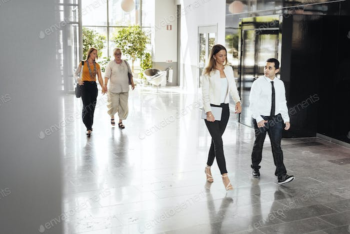 Four colleagues walking inside office building lobby