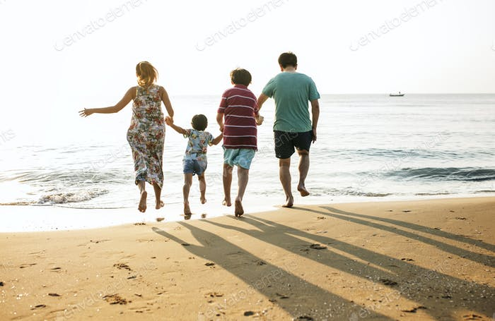 Asian family playing at the beach