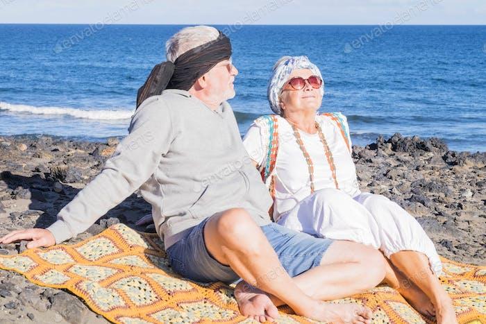 senior couple under a bright sunlight enjoy the summer day at the beach