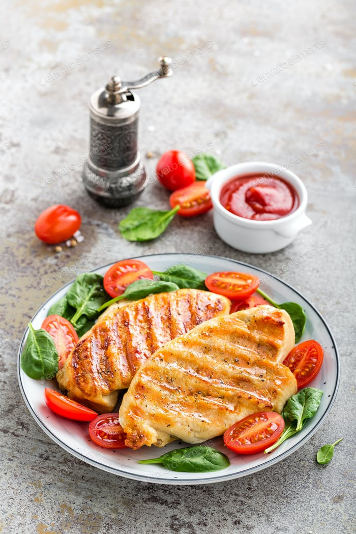 Chicken breast or fillet, poultry meat grilled and fresh vegetable salad of tomato and spinach