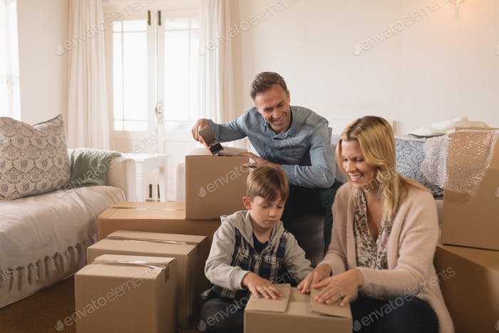 Happy family while unpacking cardboard boxes in their new home