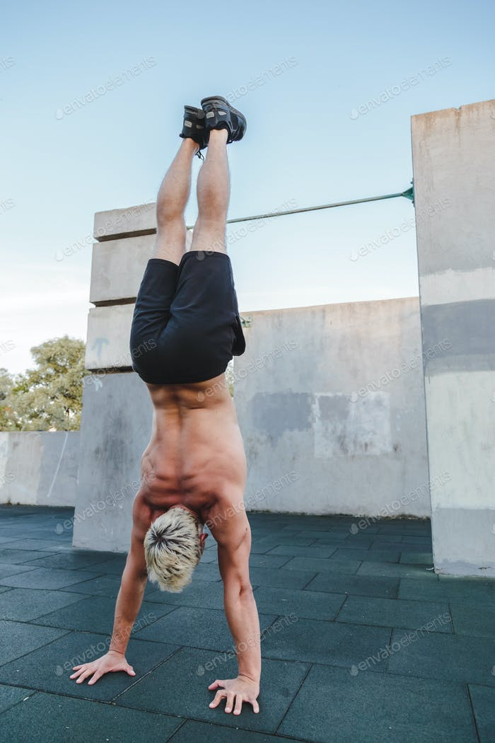 Handstand yoga pose by athlete man on the sport ground outdoors, natural lifestyle photo.