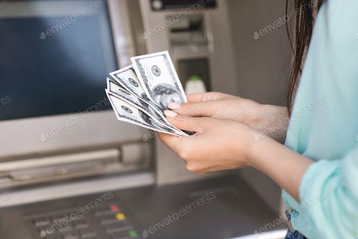 Nahaufnahme der weiblichen Hand Zählen Dollargeld Bargeld in der Nähe von Straße atm
