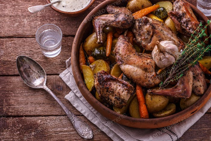 Oven baked rabbit with root vegetables and herbs, rustic style