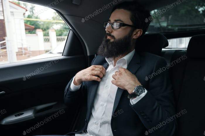 Confident businessman sitting on the car back sit