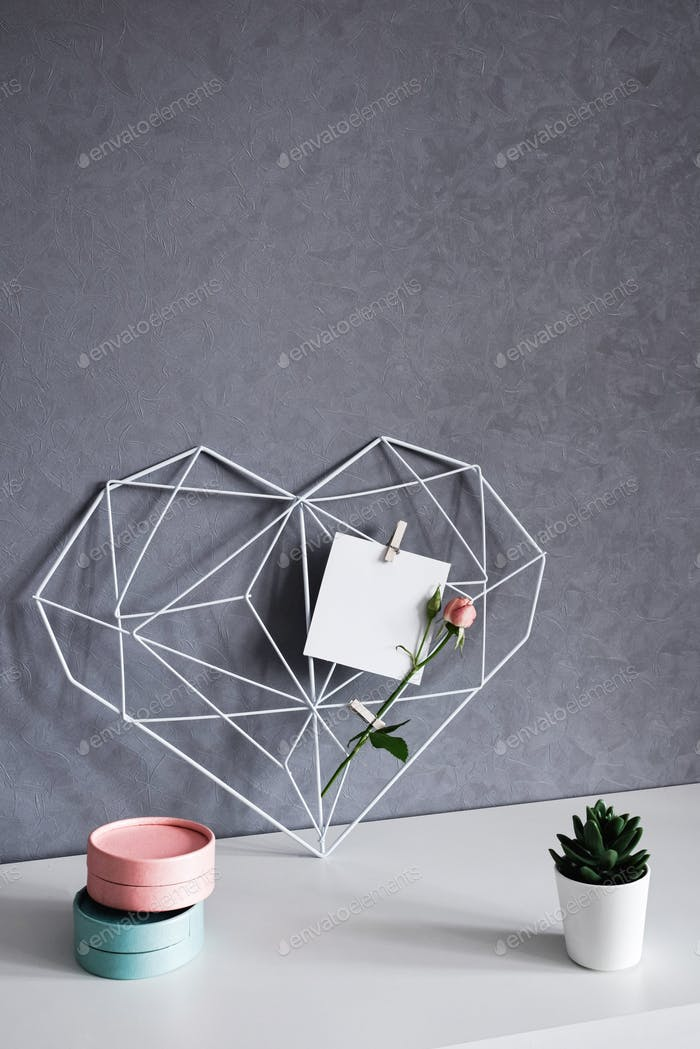 Graceful openwork heart with notes on concrete wall background. Minimalism