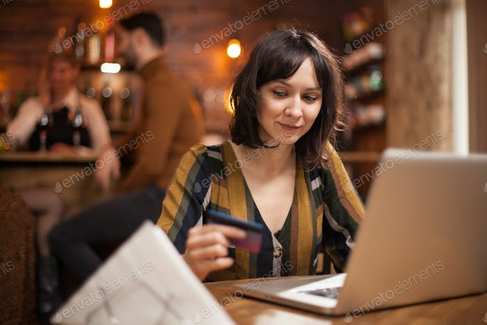 Beautiful young woman holding credit card and using laptop for online purchasing