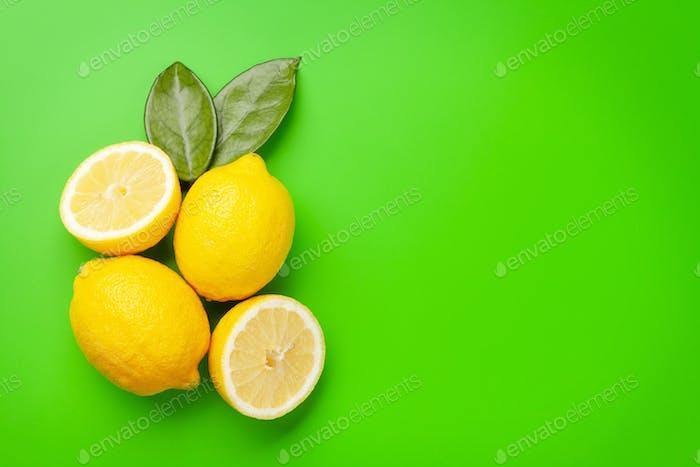 Fresh ripe lemon on green background