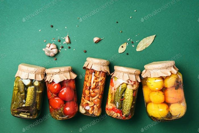 Konserviertes und konserviertes Gemüse in Gläsern über grünem Hintergrund. Draufsicht. Flache Lag. Kopierbereich