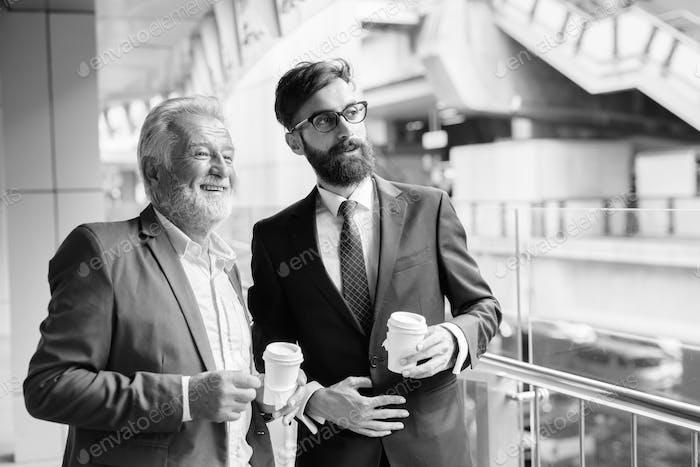 Multi ethnic bearded businessmen together around the city