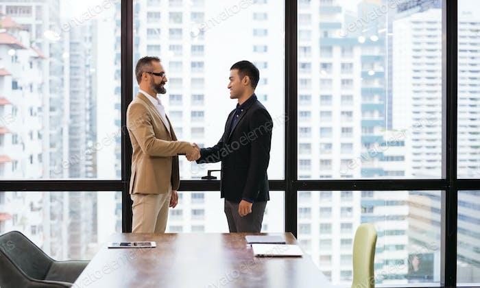 Hombre de negocios caucásico apretando las manos con el socio de la empresa o cliente
