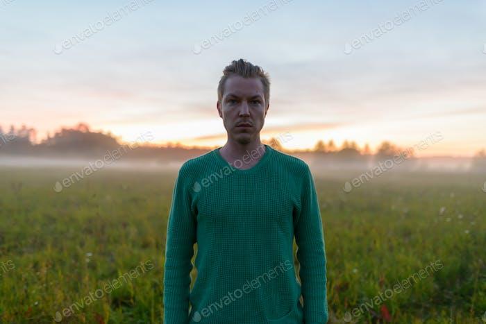Junge gut aussehende kaukasischen Mann in der schönen Landschaft von nebligen Gras Feld in der Pause der Morgendämmerung