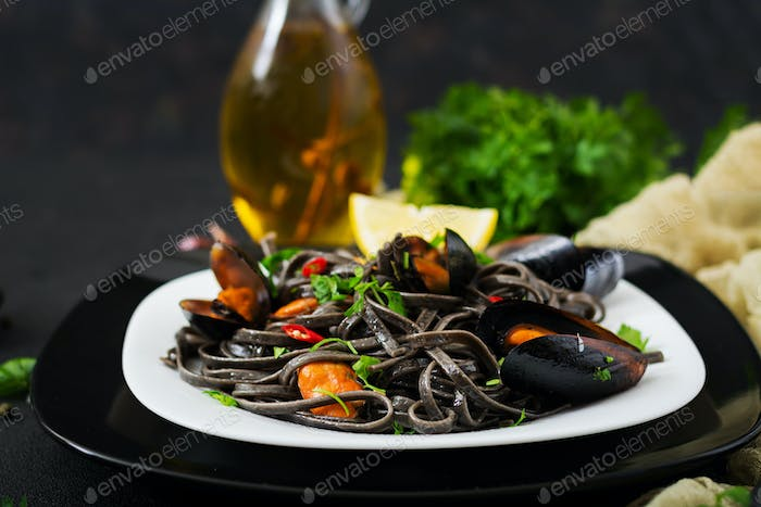 Black spaghetti. Black seafood pasta with mussels over black background. Mediterranean delicacy food