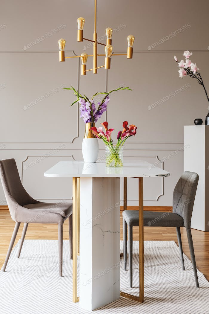Flowers on table in grey dining room interior with gold lamp and