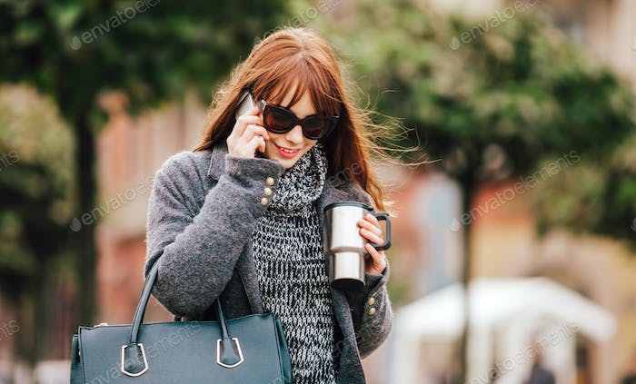 Smiling woman talking on mobile phone in the city