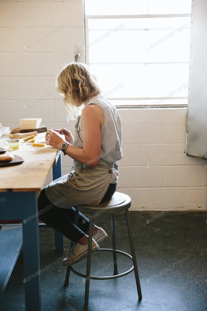 A woman sitting on a stool in a workshop.