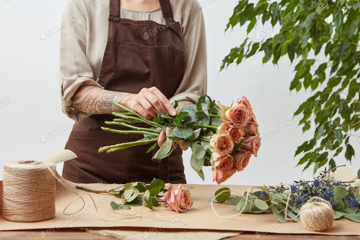 Female florist making beautiful bouquet from living coral color roses on a light background. Process