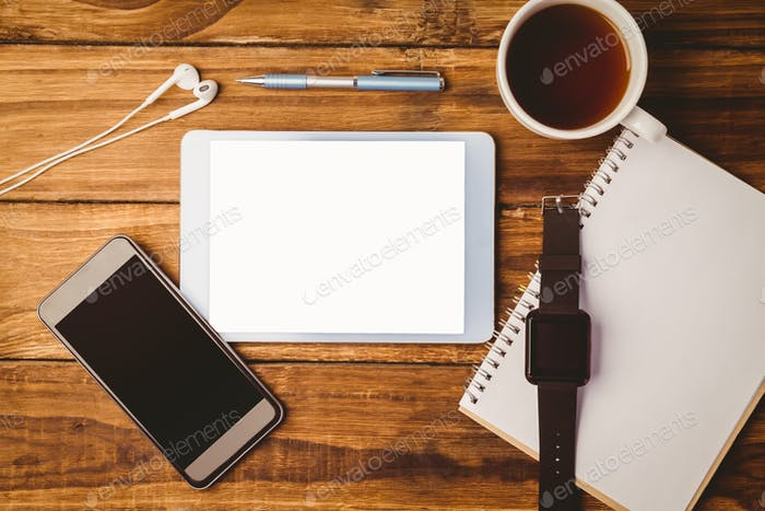 `Tablet ans smartphone and swatch on notepad next to cup of coffee on wooden table