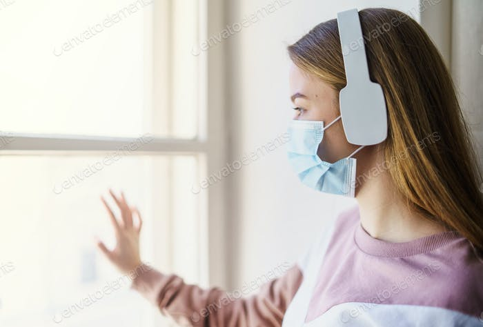 Young woman with face mask and headphones indoors, looking through window