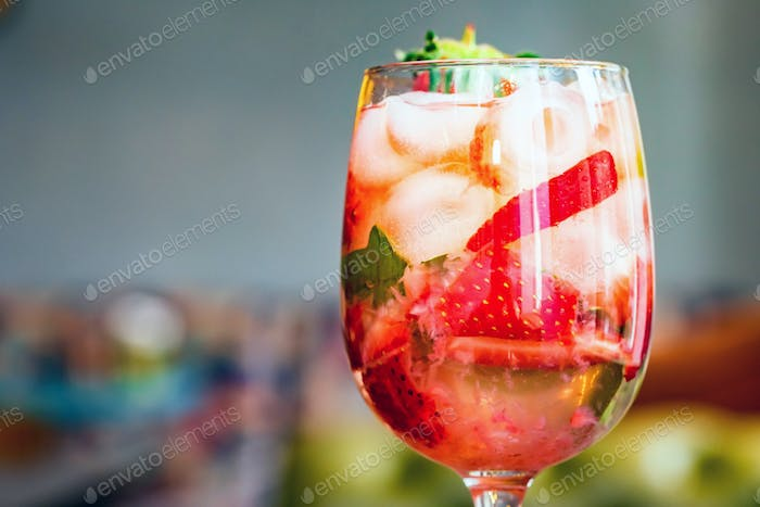 Glass with homemade srawberry mojito and berries on wood