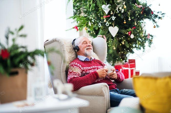 Ein Porträt von Senior Mann mit Kopfhörern sitzt auf Sessel zu Hause zu Weihnachten Zeit.