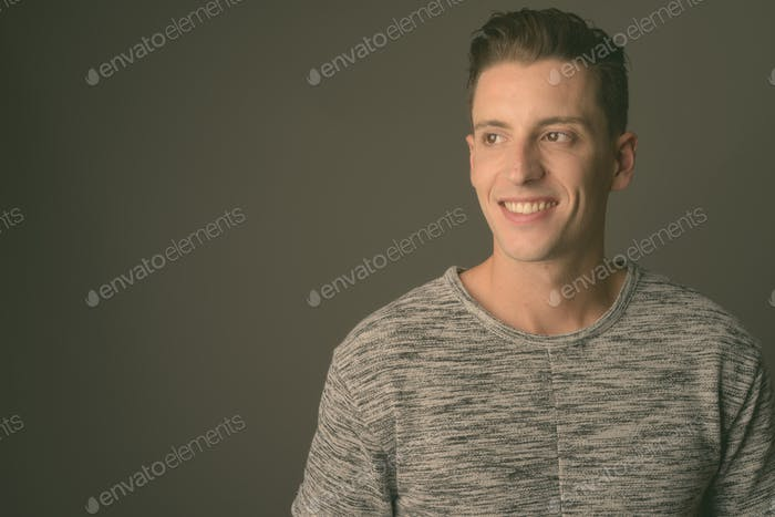 Young handsome man wearing gray shirt against gray background