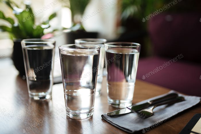 Close up photo of glasses with water on table in restaurant