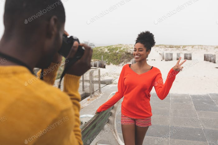 Man capturing photo of pretty woman while standing at pavement and posing peace sign on a sunny day