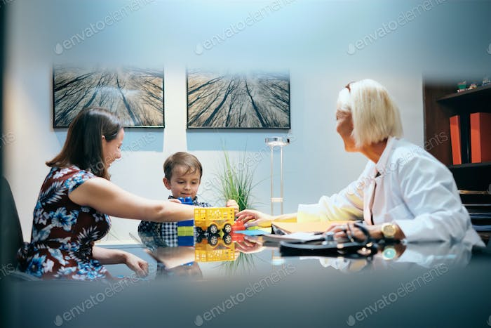 Happy Doctor Woman Working And Playing With Mom And Boy