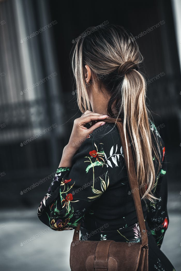 Happy young beautiful woman walking in city street Stylish fashion model wearing floral print dress