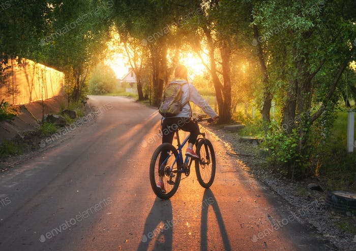 Woman riding a bicycle on the rural road at sunset in summer