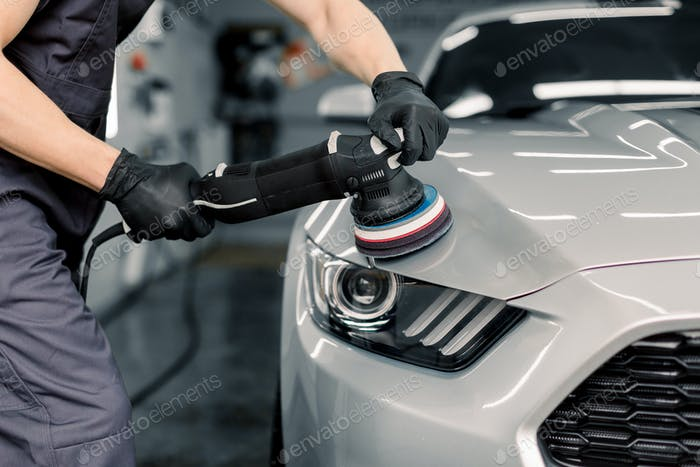 Car detailing and polishing concept. Hands of professional car service male worker, with orbital