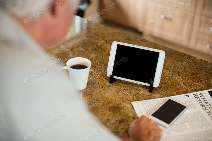 Senior man looking at digital tablet in the kitchen