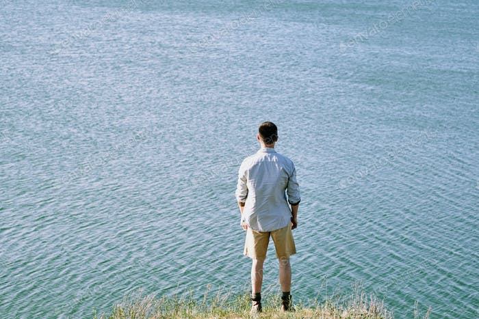 Rear view of young male traveler in shirt and shorts standing on riverbank