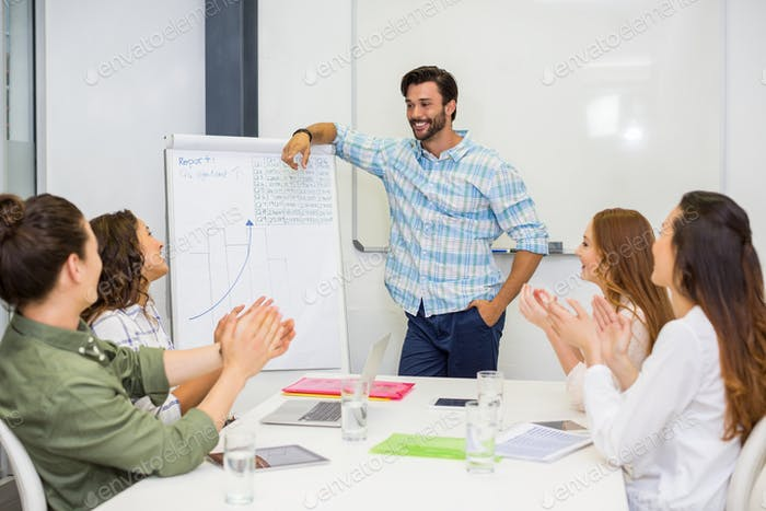 Executives appreciating their colleague during presentation in conference room