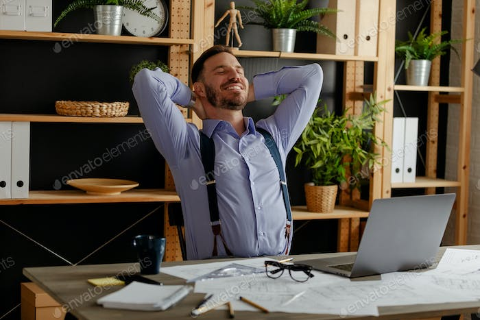 Architect freelancer working with blueprints in workspace office, holding hands behind head.